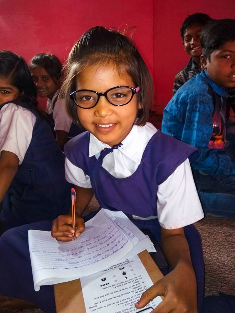 Young schoolgirl doing her work whilst wearing spectacles