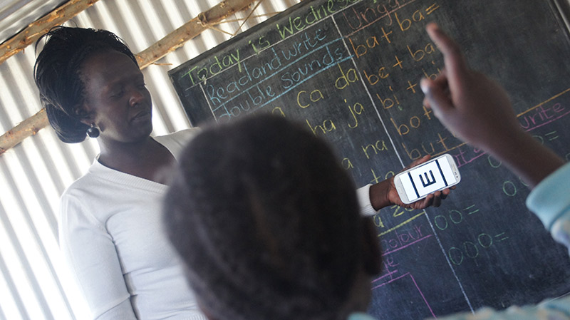 A female teacher in Kenya holding up a smartphone in front of the blackboard, testing vision of a female student